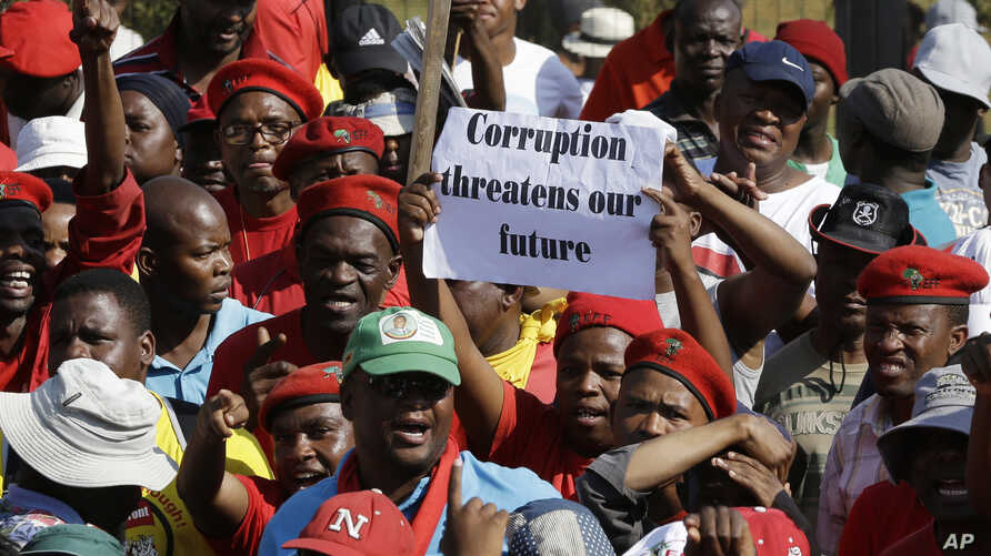 FILE - Protesters hold a placard demanding an end to corruption at a rally in Pretoria, South Africa, Sept. 30, 2015.