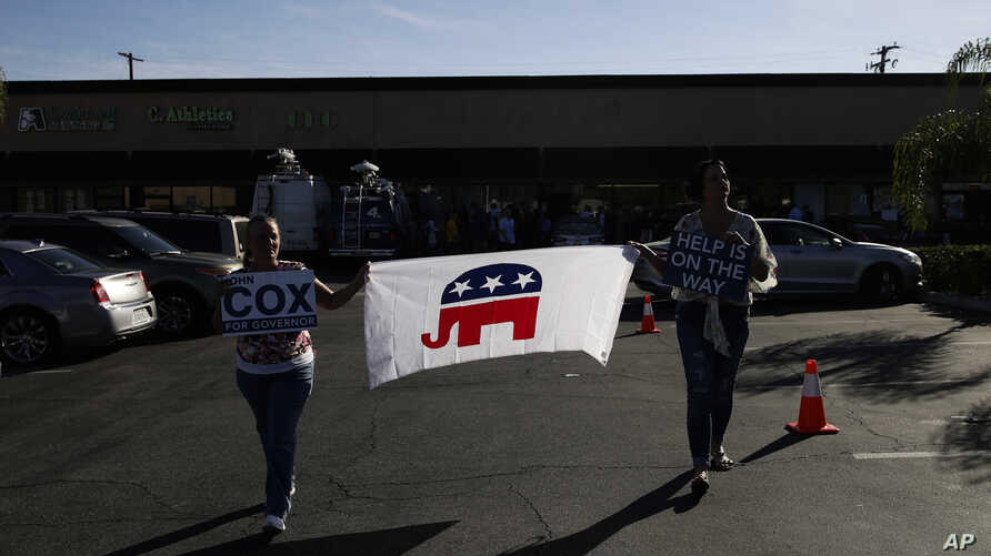 FILE - Supporters carry a flag displaying the elephant symbol of the Republican party campaigning for candidates for office, in Rowland Heights, California, Nov. 3, 2018.