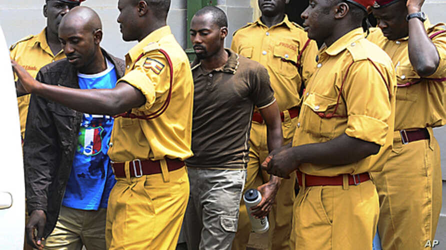 Rwandan citizen Muhamoud Mugisha, right, and his co-accused Ugandan Edris Nsubuga, left, leave the Kampala High Court after their judgment, in Kampala, Uganda, Sept.16, 2011.