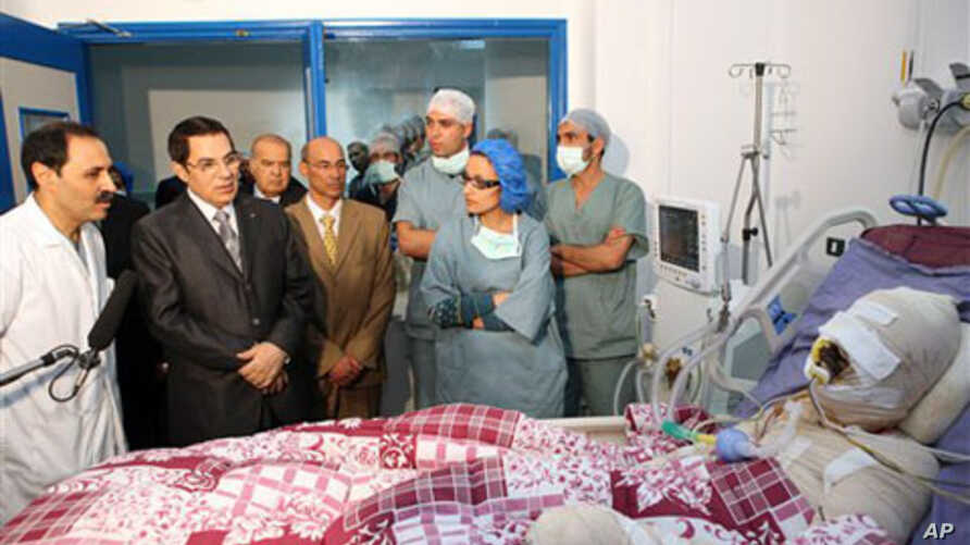 In this photo released 28 Dec 2010 by the Tunisian President's office, Tunisia's President Zine El Abidine Ben Ali, second from left, visits Mohamed Bouazizi, a young man who set himself on fire after police confiscated fruit and vegetables he sold w