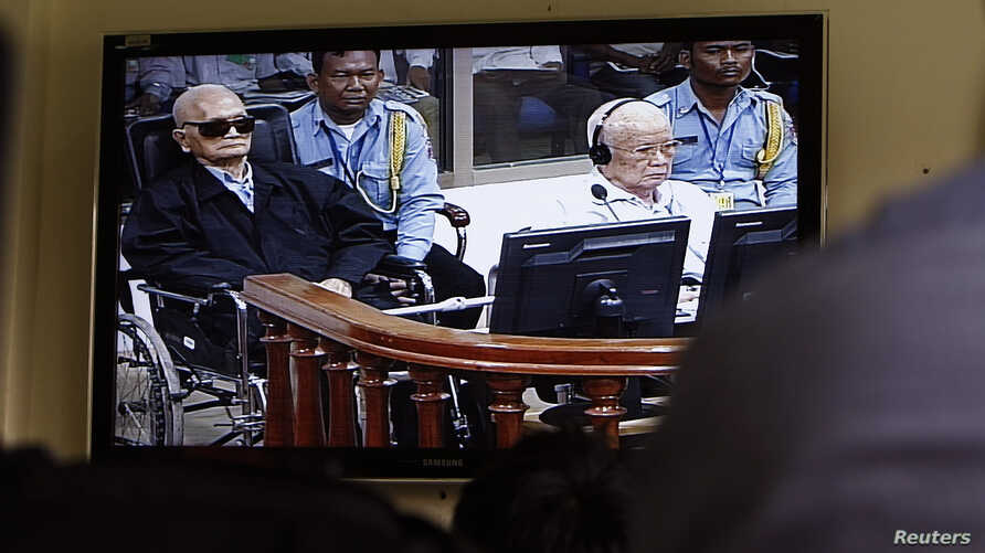 FILE - Khieu Samphan, second from right, former Khmer Rouge head of state, and Noun Chea, left, who was the Khmer Rouge's chief ideologist and No. 2 leader, are seen on a screen at the court's press center of the U.N.-backed war crimes tribunal in Ph