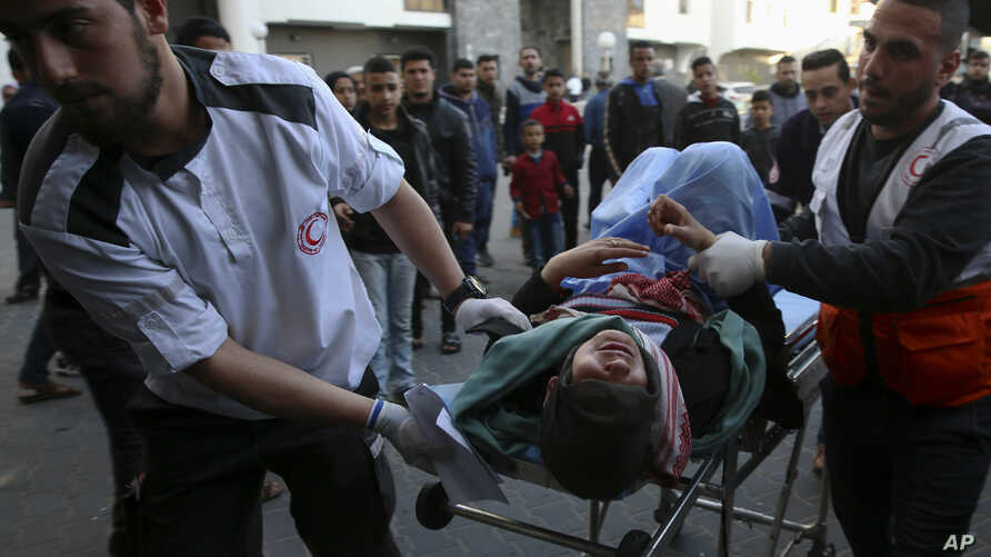 Medics move a wounded youth, who was shot by Israeli troops during a protest at the Gaza Strip's border with Israel, into the treatment room of Shifa hospital in Gaza City, Friday, March 22, 2019.