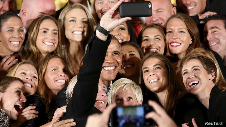 U.S. President Barack Obama poses for a selfie taken by veteran star player Abby Wambach as he welcomes the United States Women's National Soccer Team to the White House in Washington to honor their victory in the 2015 FIFA Women's World Cup, October