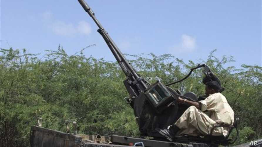 A Somali government soldier on a truck manning an anti aircraft gun takes up position during clashes with Islamist insurgents in southern Mogadishu's Hodon neighborhood , Somalia, 3 Oct 2010