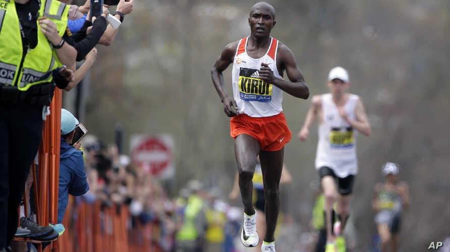 Geoffrey Kirui of Kenya leads Galen Rupp of the United States and the rest of the field along the course of the 121st Boston Marathon in Brookline, Massachusetts, April 17, 2017.