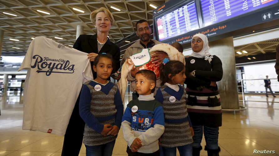FILE - U.S Ambassador to Jordan Alice Wells,poses with the family of Syrian refugee Ahmad al Aboud, at the Queen Alia International Airport in Amman, Jordan, April 6, 2016. The family was headed for resettlement in the United States.