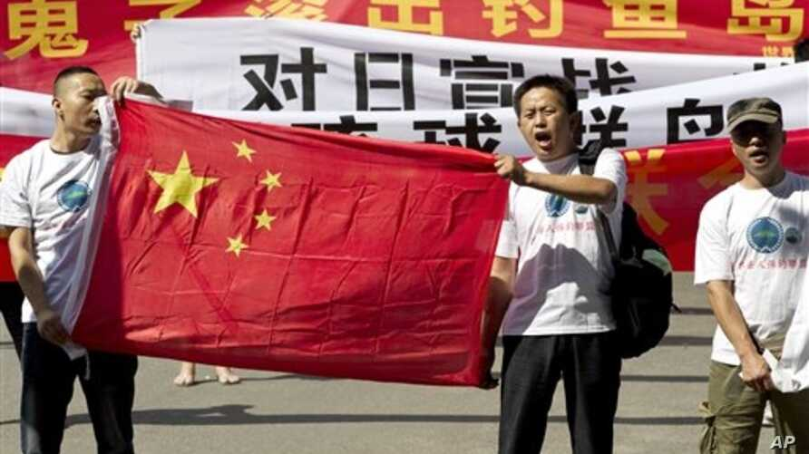 """Chinese protesters hold banners reading """"Declare war against Japan"""" and """"Japan get out of Diaoyu islands"""" during a protest outside the Japanese Embassy in Beijing Aug. 15, 2012."""