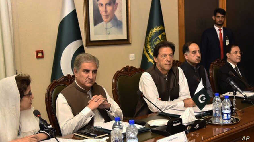In this photo released by the Press Information Department, Pakistani Prime Minister Imran Khan, center, attends a briefing at the Foreign Ministry in Islamabad, Pakistan, Aug. 24, 2018. Pakistani Foreign Minister Shah Mehmood Qureshi is seen second