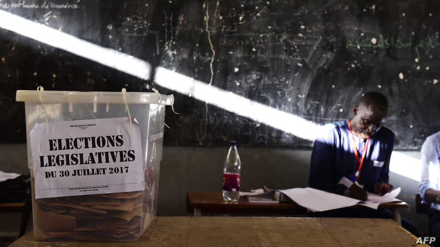 FILE - An election helper sits next to an urn filled with ballots at a polling station in Dakar, July 30, 2017, during parliamentary elections.