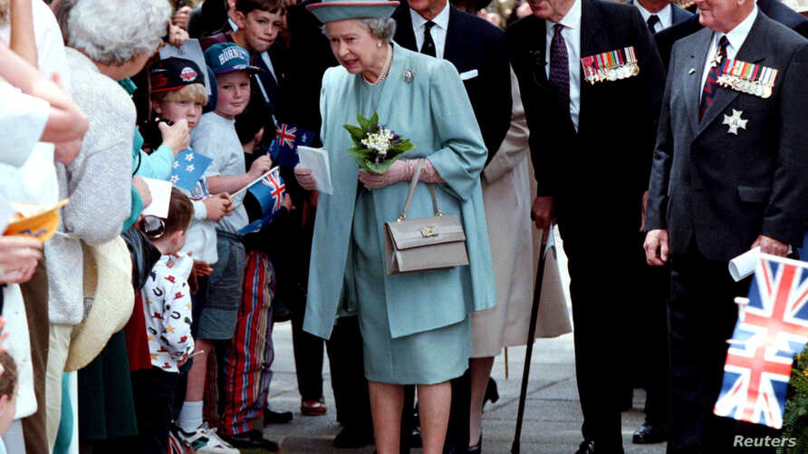 FILE - Queen Elizabeth (C) receives flowers and letters from the public as she walks with the Duke of Edinburgh (center rear) following a ceremony honoring World War II veterans in Wellington, New Zealand, Nov. 5, 1995.