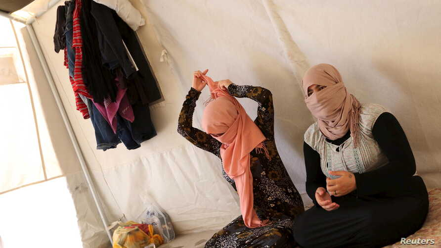 Yazidi sisters, who escaped from captivity by Islamic State (IS) militants, sit in a tent at Sharya refugee camp on the outskirts of Duhok province, Iraq, July 3, 2015.