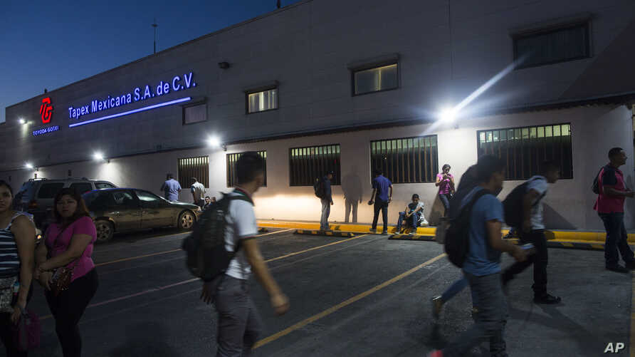 "FILE - Workers gather outside a ""maquiladora"" for car accessories in Matamoros, Mexico, March 21, 2017. A strike at 48 plants in Matamoros is heading for victory, bringing pay raises for laborers who make less than $1 an hour assembling auto componen"