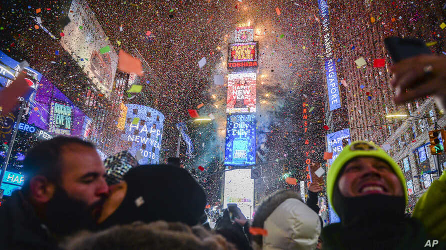 People celebrate as confetti falls down after the countdown to midnight in Times Square, Jan. 1, 2018, in New York.