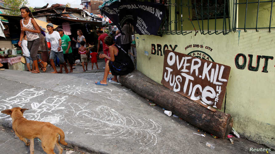 "A sign reading ""Overkill Justice for Eric"" is displayed at the entrance of a street where Eric Quintinita Sison was killed in Pasay city, Metro Manila in the Philippines, Aug. 29, 2016. Family members of Sison said he was attempting to surrender when"