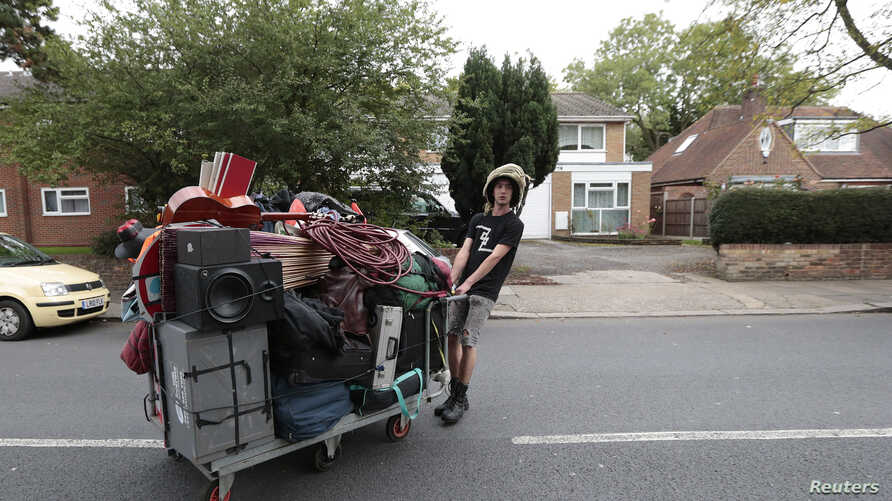 FILE - A squatter moves his belongings after being evicted from a housing estate in north London, Britain Sept. 24, 2015.