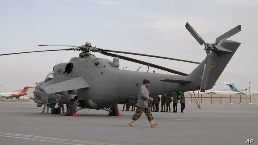 An Afghan soldier walks past Indian-donated helicopters to Afghanistan at the Kabul airport  in Kabul, Afghanistan, Dec. 25, 2015.