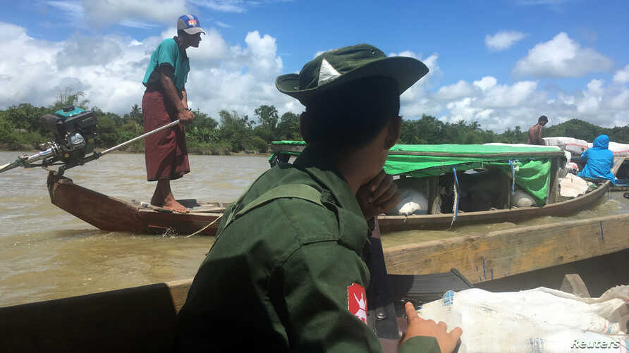 A Myanmar soldier patrols in a boat at the Mayu river while boats deliver food to isolated communities near Buthidaung in the north of Rakhine state, Sept. 13, 2017.