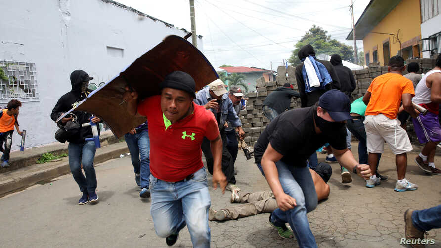 Demonstrators take cover as police fire at them during a protest against the government of Nicaraguan President Daniel Ortega in Masaya, Nicaragua, June 19, 2018.
