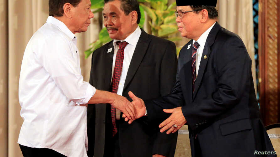 Philippine President Rodrigo Duterte. left, greets Moro Islamic Liberation Front (MILF)chairperson Al Haj Murad Ebrahim, right, while Mohagher Iqbal, MILF peace panel chairman looks on during a handover of a draft law of the Bangsamoro Basic Law (BBL