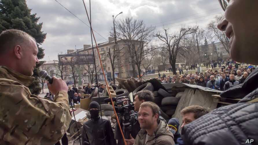 A pro-Russian activist speaks to other protesters at barricades in front of a security service regional office in Luhansk, Ukraine, April 9, 2014.
