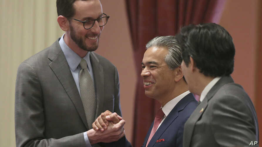 State Sen. Scott Wiener, D-San Francisco, left, receives congratulations from Assemblyman Rob Bonta, D-Alameda, center, and Sen. Kevin de Leon, D-Los Angeles, right, after his net neutrality bill was approved by the state Senate, Aug. 31, 2018, in Sa