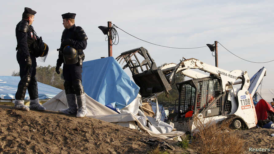 """French CRS riot police secure the area as a bulldozer tears down makeshift shelters during the dismantlement of the camp called the """"Jungle"""" in Calais, France, Oct. 27, 2016."""