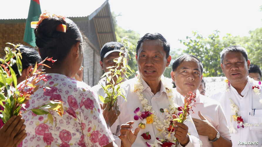 A woman presents flowers to former Myanmar ruling Union Solidarity and Development Party (USDP) chief Shwe Mann, as he campaigns at a village near his hometown Kanyuntkwin, Myanmar, Nov. 4, 2015. Myanmar will hold its historic general election on Nov