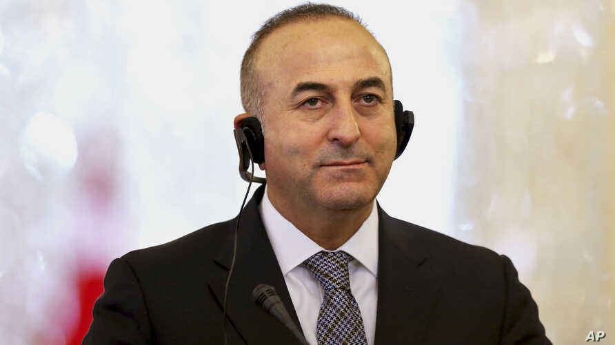 Turkish Foreign Minister Mevlut Cavusoglu listens to translation of a question in a joint press conference with his Iranian counterpart Mohammad Javad Zarif in Tehran, Iran, Dec. 17, 2014.