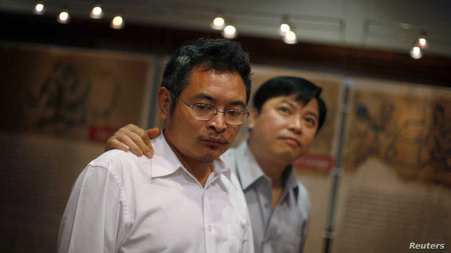 Chinese dissidents Yu Dongyue (L) and Lu Decheng walk through the Laogai Museum, which documents China's forced labor camp system, in Washington, June 2, 2009.