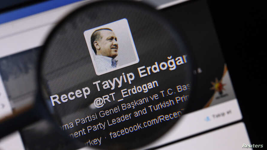 An image of Turkish Prime Minister Tayyip Erdogan on a Twitter account is pictured through a magnifying glass in this illustration picture taken in Istanbul March 21, 2014.