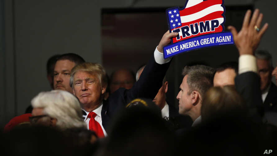Republican presidential candidate, businessman Donald Trump, holds one of his signs after a rally coinciding with Pearl Harbor Day at Patriots Point aboard the aircraft carrier USS Yorktown in Mt. Pleasant, S.C., Monday, Dec. 7, 2015.