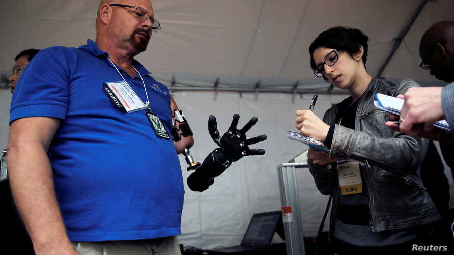 A journalist takes notes while talking with Johnny Matheny (L), from the Johns Hopkins University Applied Physics Lab, as he shows his prosthetic hand during the DARPA (Defense Advanced Research Projects Agency) Demo Day exhibition at the Pentagon in