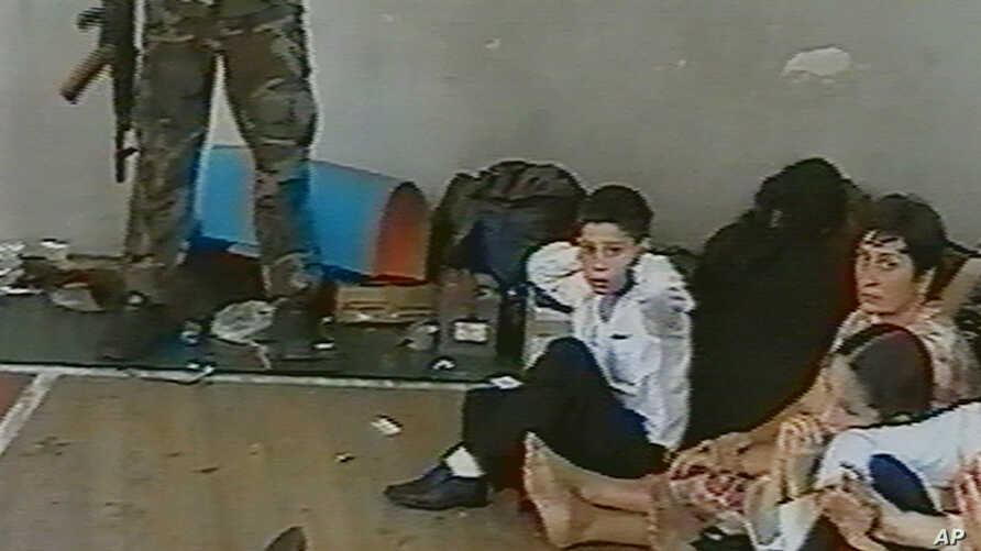 FILE - In an undated image taken from television early during the siege, hostages sit on a floor in a gym as a hostage-taker stands with his left foot on a book, apparently with a device connected to a chain of explosives, in the school in Beslan, Ru
