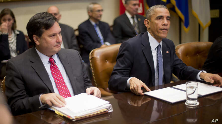 President Barack Obama, meeting with national security and public health teams about the U.S. Ebola response, sits beside Ebola response coordinator Ron Klain, left, at the White House, Nov. 18, 2014.