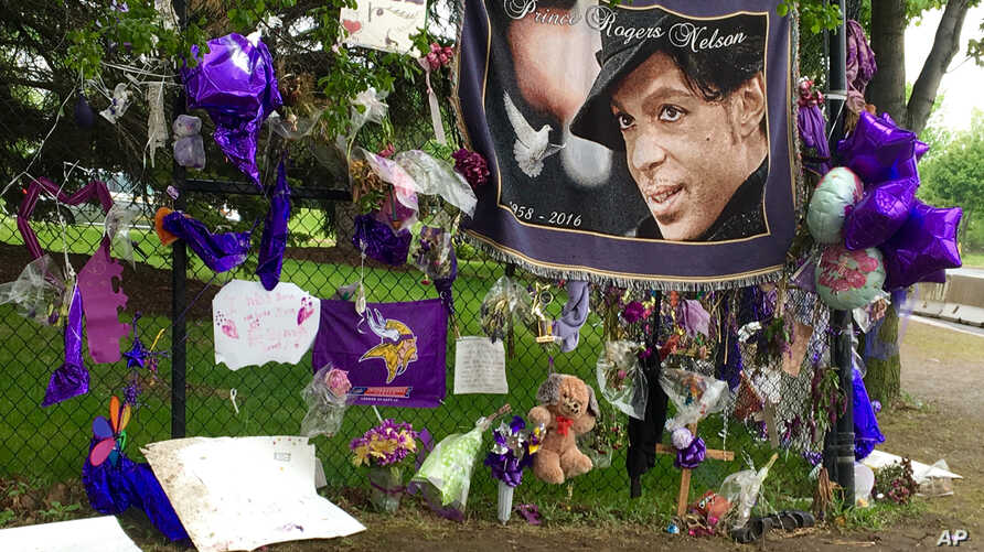FILE - Items left by fans at a memorial for musician Prince hang from a fence outside Paisley Park, May 11, 2016, in Chanhassen, Minnesota.
