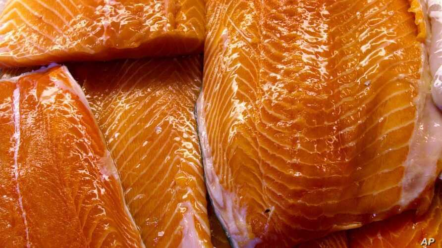 FILE - In this Apr. 25, 2003 file photo, fillets of farm-raised salmon are sprayed with water at a fish market in Portland, Maine. The Food and Drug Administration notes that manufacturers have to declare on labeling if color additives were used for