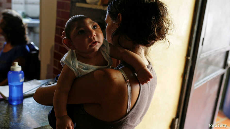 FILE - Ericka Torres holds her 3-month-old son, Jesus, who was born with microcephaly, at their home in Guarenas, Venezuela, Oct. 5, 2016.