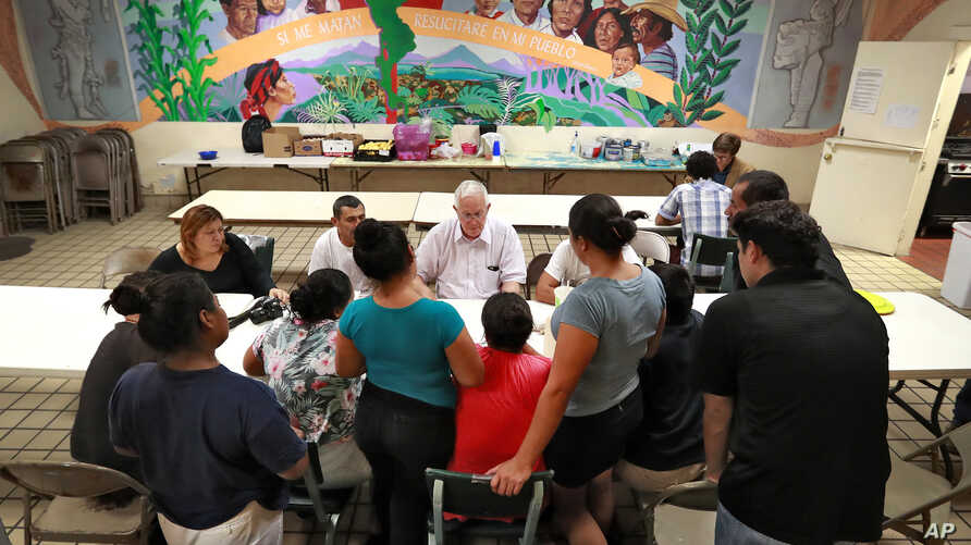 Ruben Garcia, director of the Annunciation House, speaks with migrant parents, June 26, 2018, in El Paso, Texas