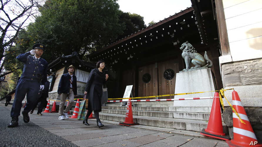 A police officer patrols around the Yasukuni shrine in Tokyo after an explosion went off, Nov. 24, 2015.
