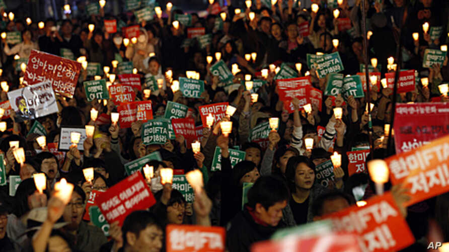 South Korean protesters hold candles during a rally against a Free Trade Agreement (FTA) between South Korea and the United States in Seoul, South Korea, Nov. 5, 2011.
