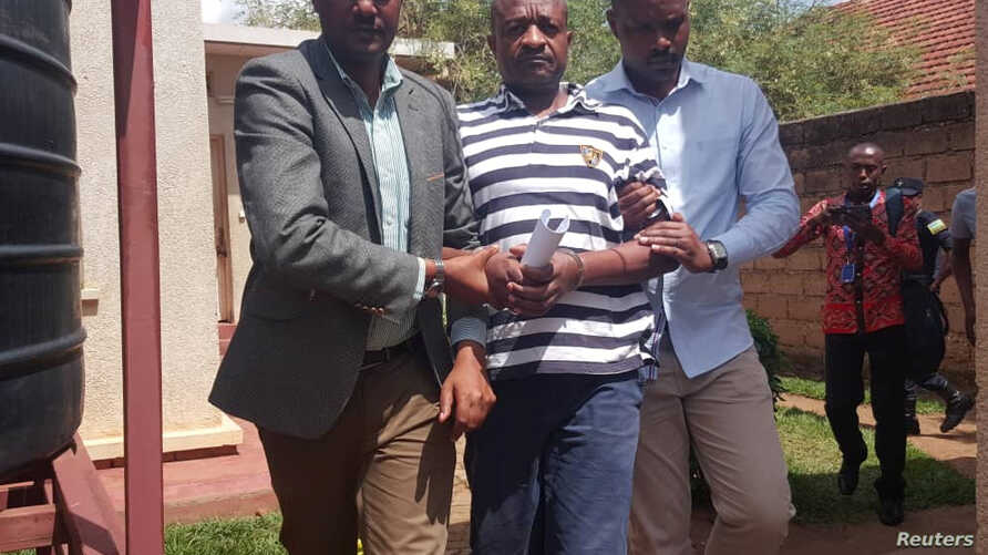 FDLR spokesperson, La Forge Fils Bazeye who was deported by the Democratic Republic of Congo to Rwanda is led away by Rwandan security members after appearing on charges of terror related accusations in a court Kigali, Rwanda, Apr. 8, 2019.