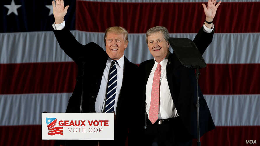 """U.S. President-elect Donald Trump waves with John Kennedy, who won the race Saturday for a seat in the U.S. Senate  from Louisiana, during a """"Thank You USA"""" tour rally in Baton Rouge, Louisiana, Dec. 9, 2016."""