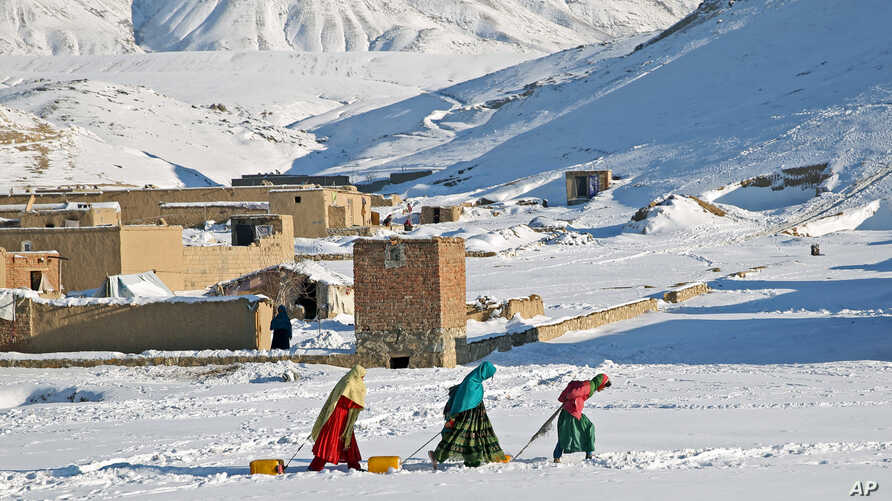 Afghan women drag containers of water on the outskirts of Kabul, Jan. 9, 2014.