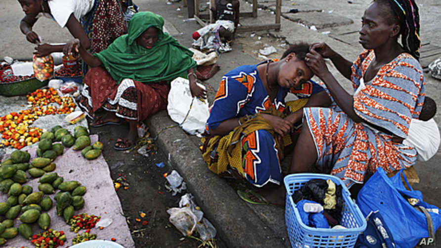 A woman braids her friend's hair at a market in the Abobo neighborhood of Ivory Coast's main city Abidjan, April 17, 2011.