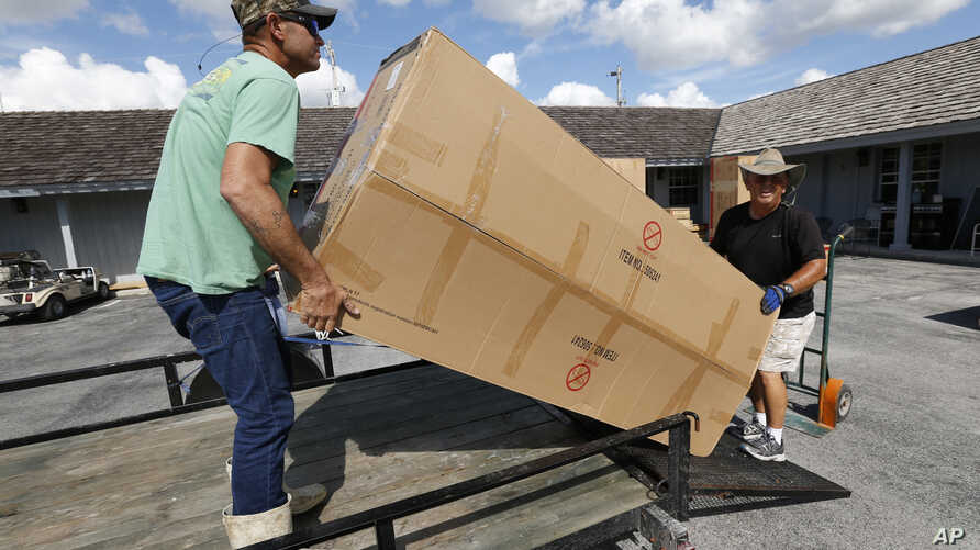 Volunteer Danny Floyd, right, of Weatherford, Okla,, helps Kenny and Brittany Smallwood, left, load new furniture donated by the nation's Churches of Christ, at Outdoor Resorts of Chokoloskee, in Chokoloskee, Fla., Nov. 9, 2017. The Smallwoods say FE