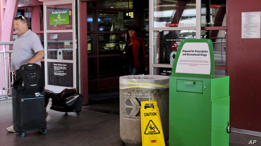 """Unidentified travelers exit the airport past a green metal container designed for """"Disposal for Prescription and Recreational Drugs,"""" set outside one of the entrances to McCarran International Airport in Las Vegas, Feb. 22, 2018."""