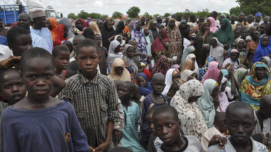 FILE - In this Tuesday Sept. 9, 2014 file photo, civilians who fled their homes following an attack by Islamist militants in Bama, take refuge at a school in Maiduguri, Nigeria.