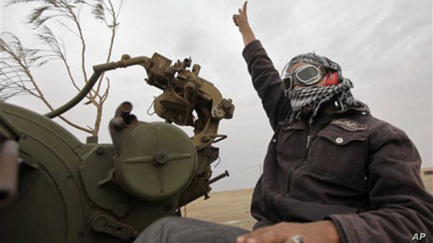 A Libyan rebel fighter manning an anti-aircraft gun flashes the victory sign as his vehicle advances towards the front line, on the outskirts of Ajdabiya, Libya, April 20, 2011