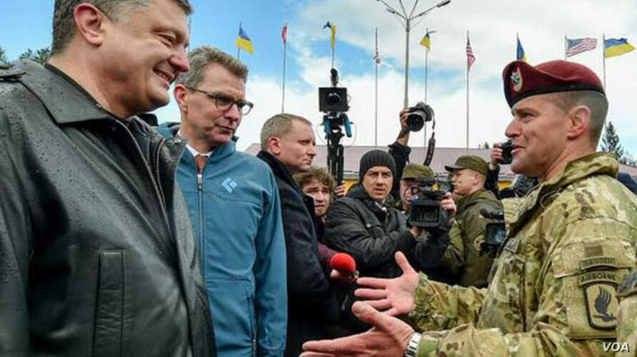 Ukrainian President Petro Poroshenko (L) speaks to an unidentified U.S. commander at the start of joint military exercises near the town of Yavoriv, Lviv region, western Ukraine, April 20, 2015. Second from left is U.S. Ambassador to Ukraine Geoffrey