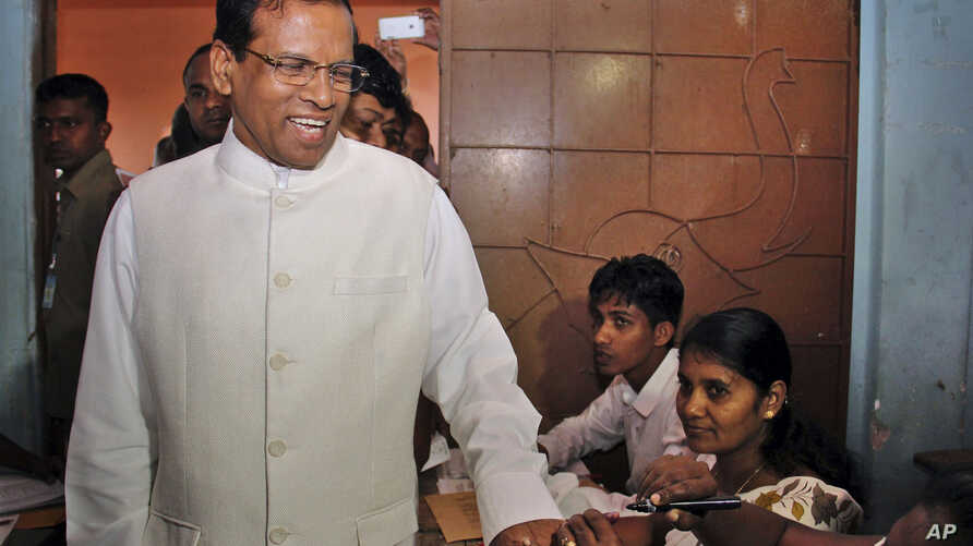 Sri Lanka's main opposition presidential candidate Maithripala Sirisena gets his finger marked with indelible ink after casting his vote at a polling station in Polonnaruwa, about 200 kilometers (124 miles) northeast of Colombo, Sri Lanka, Thursday,